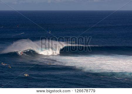 Wind surfer on wave at Peahi or Jaws surf break, Maui, Hawaii, USA