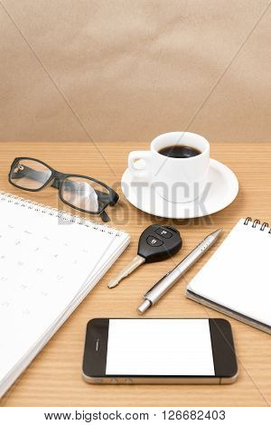 coffee and phone with car key eyeglasses notepad calendar on wood background