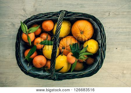 Various Fresh Citrus Fruits In Basket On Old Wooden Background