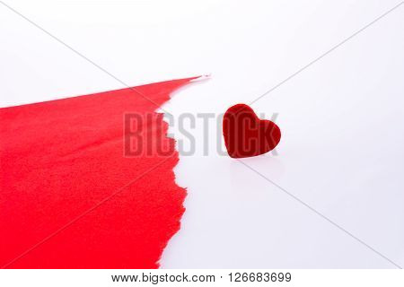 Red heart shape icon by the side of a torn paper