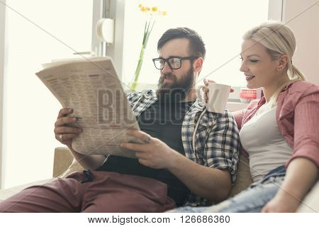 Young couple in love sitting on a couch in their apartment next to the window enjoying their free time reading newspaper and drinking coffee. Lens flare effect on window