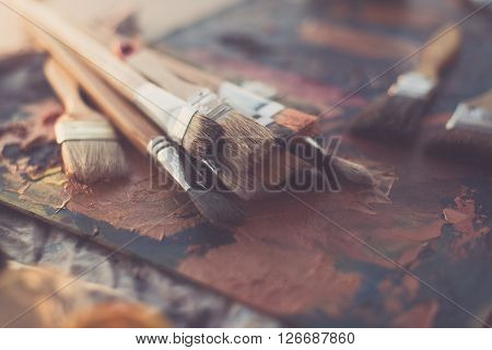 Side view of pallet with oil paint brushstrokes under paintbrush set in an art studio