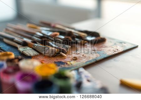Close-up side view picture of a wooden paintbrush collection lying on old palette and gouache set in the workroom with natural light
