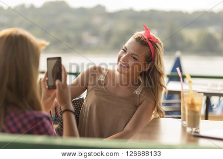 Beautiful young girls sitting in an outdoor cafe drinking coffee and faving fun photographing each other