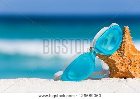 Sport Swimming Glasses And Starfish On White Sand Against Turquoise Caribbean Sea Water