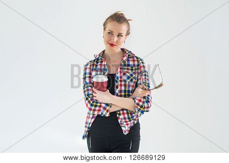 Thoughtful young woman wearing checkered shirt standing with her hands folded across the chest, holding coffee and sunglasses