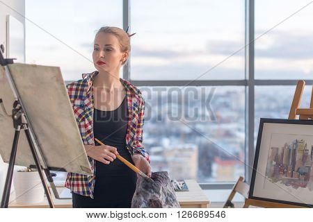 Creative female artist painting new picture, feeling inspiration, finishing drawing, using easel and paintbrush in art studio with bright natural light