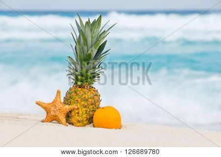 Pineapple, Orange Fruit And Starfish On Sand Against Turquoise Caribbean Sea Water