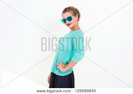 Young girl with a beautiful smile and stylish messy hairstyle wearing blue sunglasses, minty top, posing, standing sideways, looking at camera, not isolated