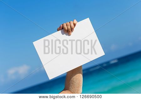 Blank White Board In Hand Against Beach View Background