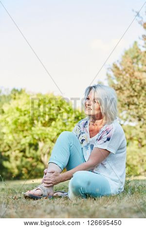Senior woman with sprained foot with pain in the park