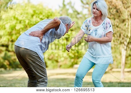 Senior woman helps man having lumbago pain in the park in summer