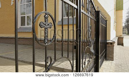 Metal fence and closed gate with cross of the churchyard. Closeup shot.