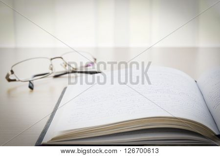 Book And Eyeglasses With On The Desk