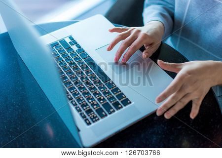 Woman's hands typing text on a laptop