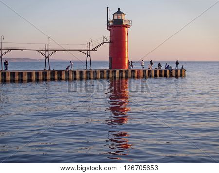 SOUTH HAVEN, MICHIGAN - April 15, 2016. People gather on the pier around the South Haven Lighthouse at the end of a warm spring day and wait for the sun to set over Lake Michigan.