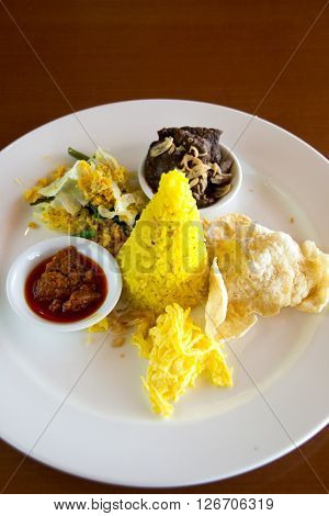 Nasi Kuning Indonesian Yellow Rice Served With Braised Beef, Shredded Egg, Vegetables, Coconut Salad
