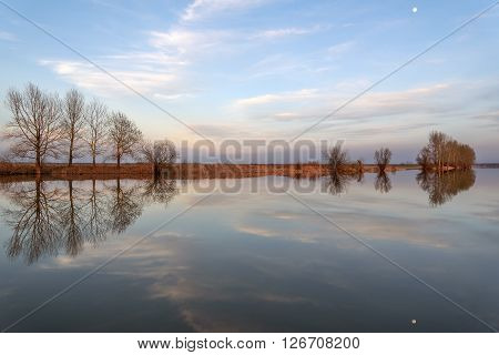 Beautiful landscape with trees blue sky clouds and the moon reflected in the smooth water of the river in the light of the setting sun