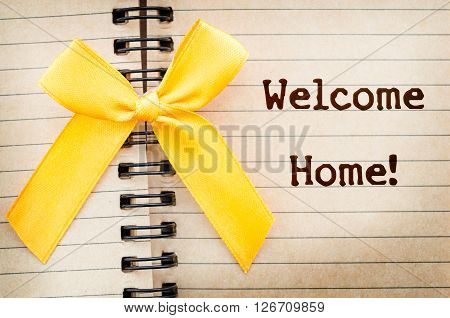 The words Welcome Home written on a old brown diary paper next to a yellow ribbonin reference to military returning from overseas duty.