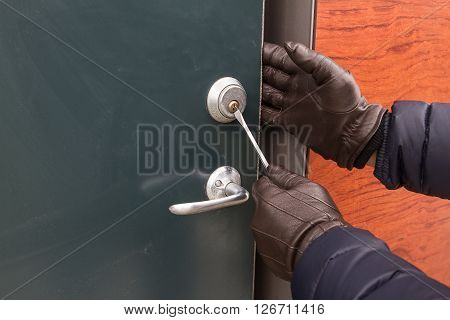 Breaking into houses with a special tool.