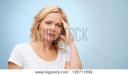 people, healthcare, stress and problem concept - unhappy woman suffering from headache over blue background