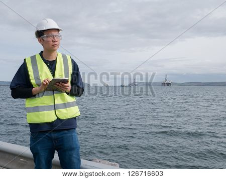 An asian engineer holding a tablet and standing in front of semi submersible oil rig