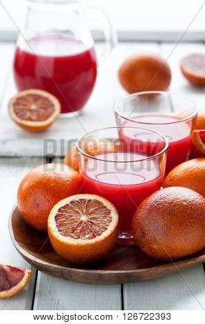 Fresh delicious juice with red oranges on wooden plate selective focus vertical