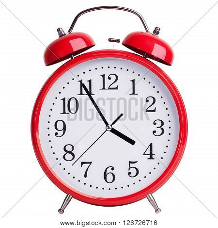 Red round alarm clock shows five minutes to four