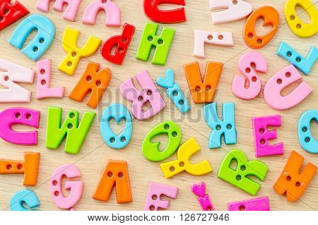 Untidy collection of plastic alphabet letters school education toy on wooden background.