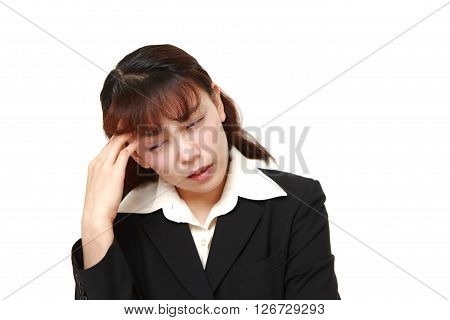 Asian businesswoman suffers from headache on white background
