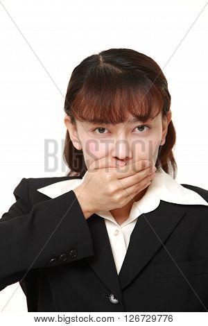 Asian businesswoman making the speak no evil gesture