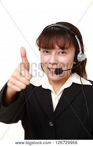 studio shot of businesswoman with thumbs up gesture