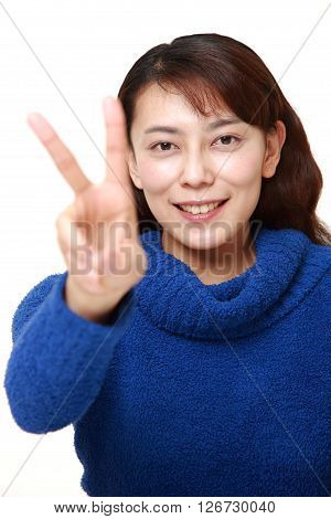 Asian woman showing a victory sign on white background