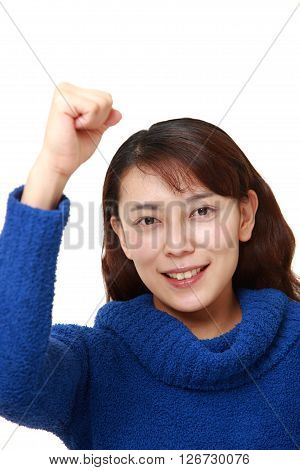 Asian woman in a victory pose on white background