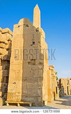 LUXOR EGYPT - OCTOBER 7 2014: The top of the Hatshepsut Obelisk is seen behind the ruined wall of the  on October 7 in Luxor.