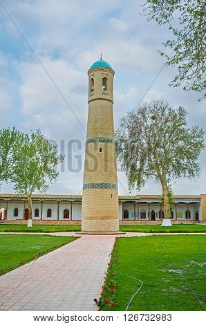The stone minaret with a smooth circular baked brick of the Jami Mosque located in the middle of the scenic Mosque's garden Kokand Uzbekistan. poster