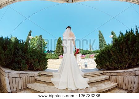 Full body of bride with bridal bouquet standing on stairs in park ander modern roof. Fisheye lens photo