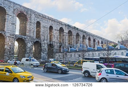 ISTANBUL TURKEY - JANUARY 21 2015: The Valens Aqueduct and the traffic on Ataturk Boulevard passing under its arches on January 21 in Istanbul.