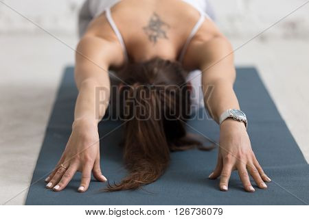 Beautiful young woman with flower tattoo on her back working out indoors. Doing forward bend yoga exercise on blue mat. Balasana. Child Pose. Ardha-Kurmasana (Half Tortoise Pose). Close-up