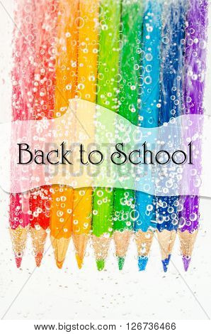 Back to school concept. Colorful wooden pencils in soda water with bubbles on white background.