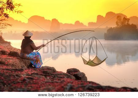 Beautiful sunrise landscape with rear view of woman fishing in morning. Lifestyle and nature concept, Phang nga province, Thailand.