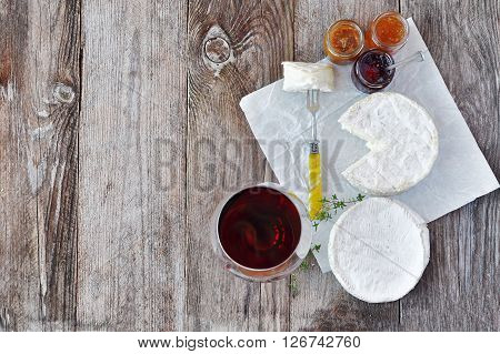 French soft cheese with a different jam and a glass of red wine on the natural wood backgraund