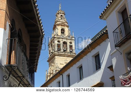 Bell tower of the mosque of Cordoba between the facades of the houses - Spain