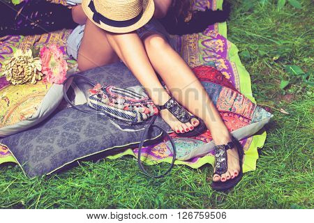 woman feet on grass in flat summer sandals lean on pillows  hat lay on legs from above