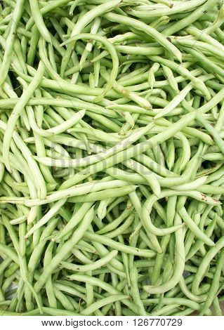 Close-up view group of fresh small, slender wax green beans or string beans, haricot vert on display at Vegetable Stall of Local Market, Little India, Singapore.