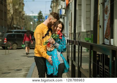 loving couple on a date embracing on a city street. The girl holding a bouquet of tulips.