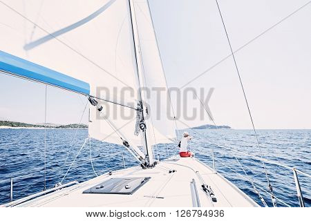Young woman wearing sunglasses and red shorts, sitting on deck under sails on yacht bow and enjoying wonderful view to islands in peaceful sea during summer sailing holidays - yacht charter concept