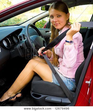 Woman fastening seat belt in her car