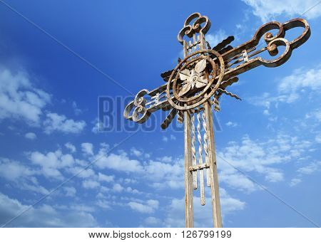 Old metal cross on a background of blue sky. With clipping path