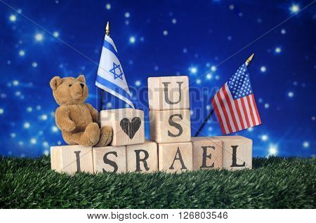 Alphabet blocks, a teddy bear and two flags declaring a friendship between Israel and the United States.  All on a bed of grass against a starry, night sky.